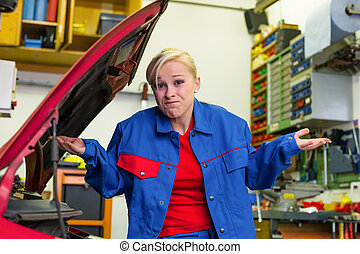 woman as a mechanic in car workshop - a young woman as a...