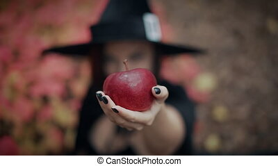 Woman as witch in black offers red apple as symbol of temptation, poison. Fairy tale concept, halloween, cosplay