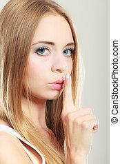 Woman asking for silence finger on lips