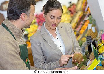 woman asking greengrocer about kiwis