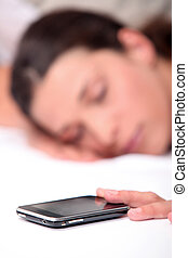 Woman asleep next to mobile telephone