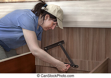 Woman assembles furniture, hinges lifting mechanism screwed to bed frame.