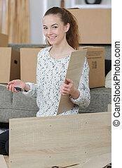 woman assembling furniture using scredriver