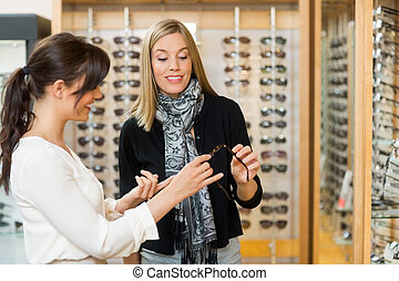 Woman Assisting Customer In Selecting Glasses - Young woman...