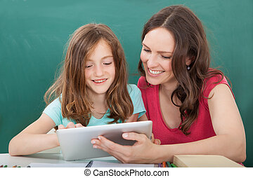Woman Assisting Girl In Using Digital Tablet