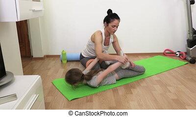Woman assisting her daughter in yoga