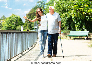 Woman Assisting Her Father While Walking In Park