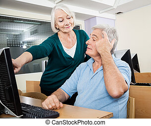 Woman Assisting Male Classmate In Computer Class - Senior...