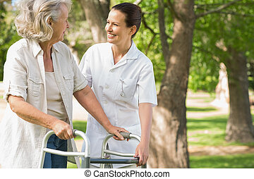 Woman assisting mature female with walker at park - Smiling...