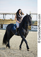 Beautiful young woman riding a horse on a hippodrome