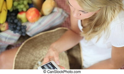 Woman at a picnic on her smartphone