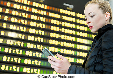 Woman at airport in front of flight information board checking her phone.