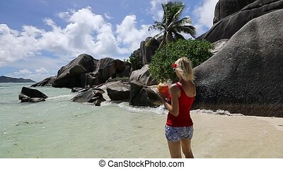 Woman at Anse Source d'Argent - Woman holding a coconut...