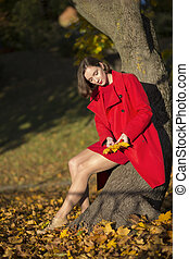 Woman at autumn park look on leaves