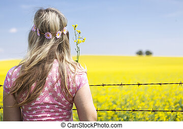 Woman at barbed wire fence looking at canola field