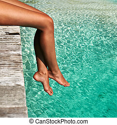 Woman at beach jetty - Woman's legs at beach jetty