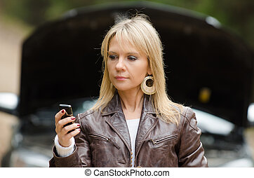 woman at broken car with phone