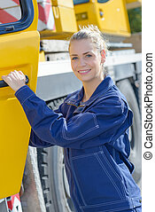 Woman at cab of heavy plant vehicle