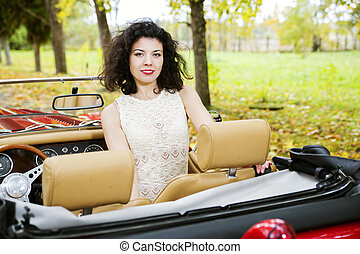 Woman at car on passanger seat at park