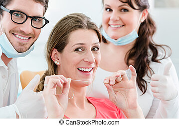 Woman at dentist using dental floss