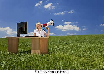 Woman At Desk With Computer Using Megaphone In Green Field