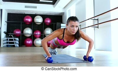 Woman at gym push up push-up workout exercise with dumbbells. Dolly shot