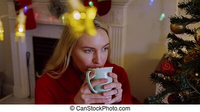 Front view of a young Caucasian woman, with decratiosn hanging in the foreground holding a cup and drinking in her sitting room at Christmas time