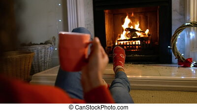 Over the shoulder view of a mixed race woman in her sitting room at Christmas, reclining in front of the fireplace, warming her feet and drinking a hot drink in a mug