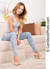 Woman at home. Beautiful young women sitting on the couch and smiling