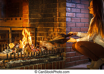 Woman at home fireplace making fire with bellows. - Woman at...