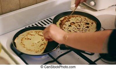 Woman at home preparing for two Pancake pans Ukraine