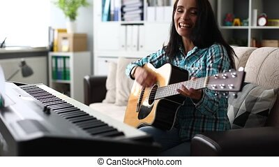Woman at home sitting on the couch playing the guitar and...
