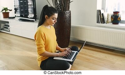 Woman at home sitting on the floor, working on laptop, writing