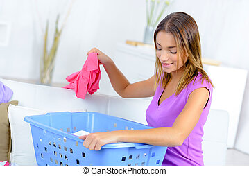 woman at home sorting laundry