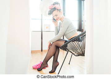 Woman at home wearing stockings taking a call on her mobile phone