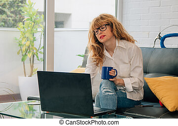 woman at home with computer and cup of coffee sitting on the sofa