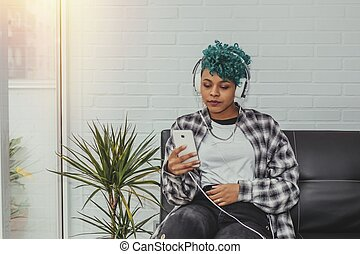 woman at home with mobile phone and headphones on the couch sitting listening to music