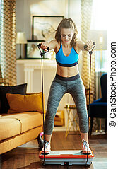 woman at modern home training using vibration power plate