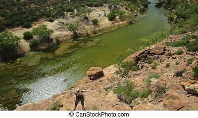 Blonde caucasian woman with open arms enjoys in the lower part of Murchison River in Kalbarri National Park, Western Australia. Happy freedom travel in the outback of Australia. Sunny in summer