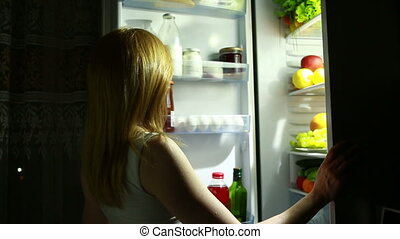 Woman at night looking into fridge. girl takes the orange.