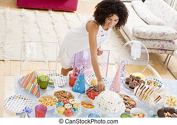 Woman at party fixing cake on food table smiling