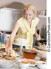 Woman at party getting tart from food table smiling