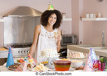 Woman at party holding drink standing by food table smiling