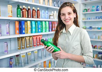 woman at pharmacy buying shampoo - happy woman at pharmacy...