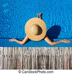 Woman at poolside - Woman in hat relaxing at the pool
