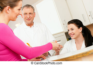 Woman at reception of clinic - Patient in reception area of...