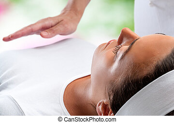 Woman at reiki session with therapist hand in background.