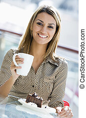Woman at restaurant eating dessert and smiling (selective focus)