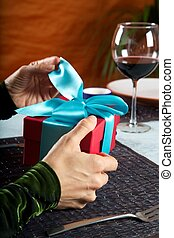opening a blue bow gift