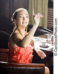 woman at restaurant - woman sits at the table and does a...